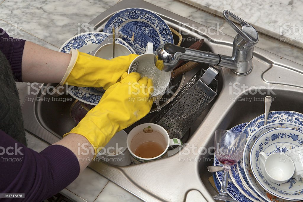 Hands in yellow gloves wash the dirty dishes stock photo