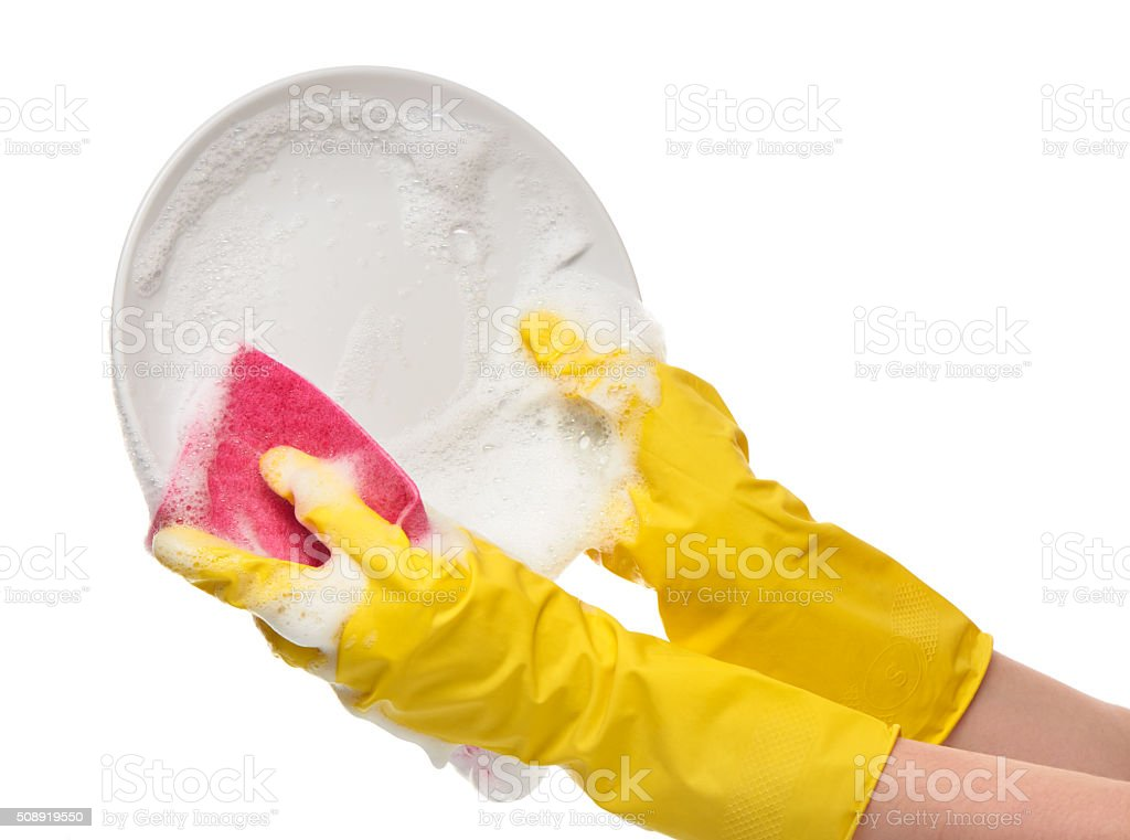 Hands in yellow gloves washing white plate with pink rag stock photo