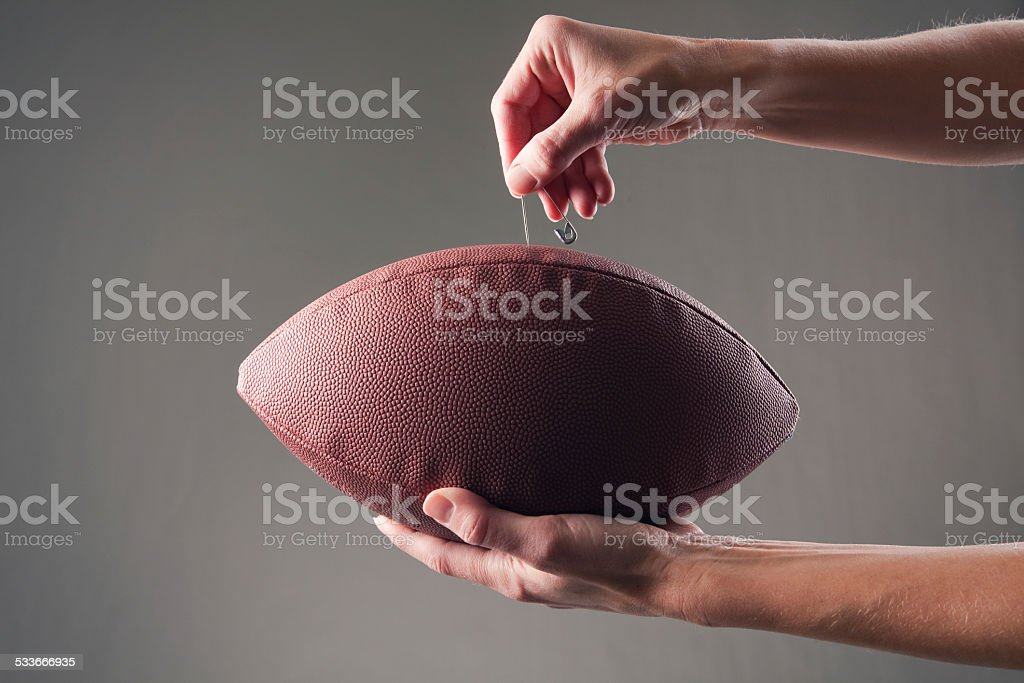 Hands Inserting a Pin Into Football To Deflate It stock photo