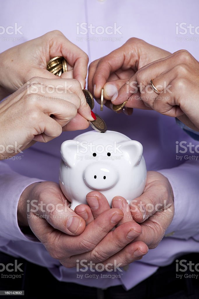 Hands inserting money in the piggybank royalty-free stock photo