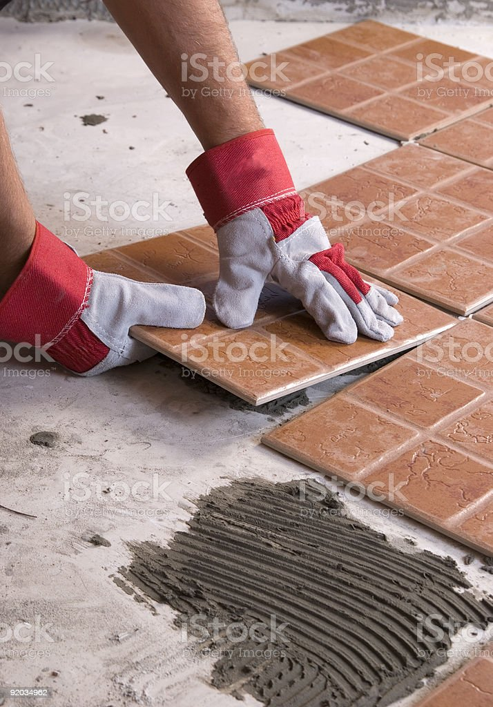 Hands installing tiles on the floor royalty-free stock photo