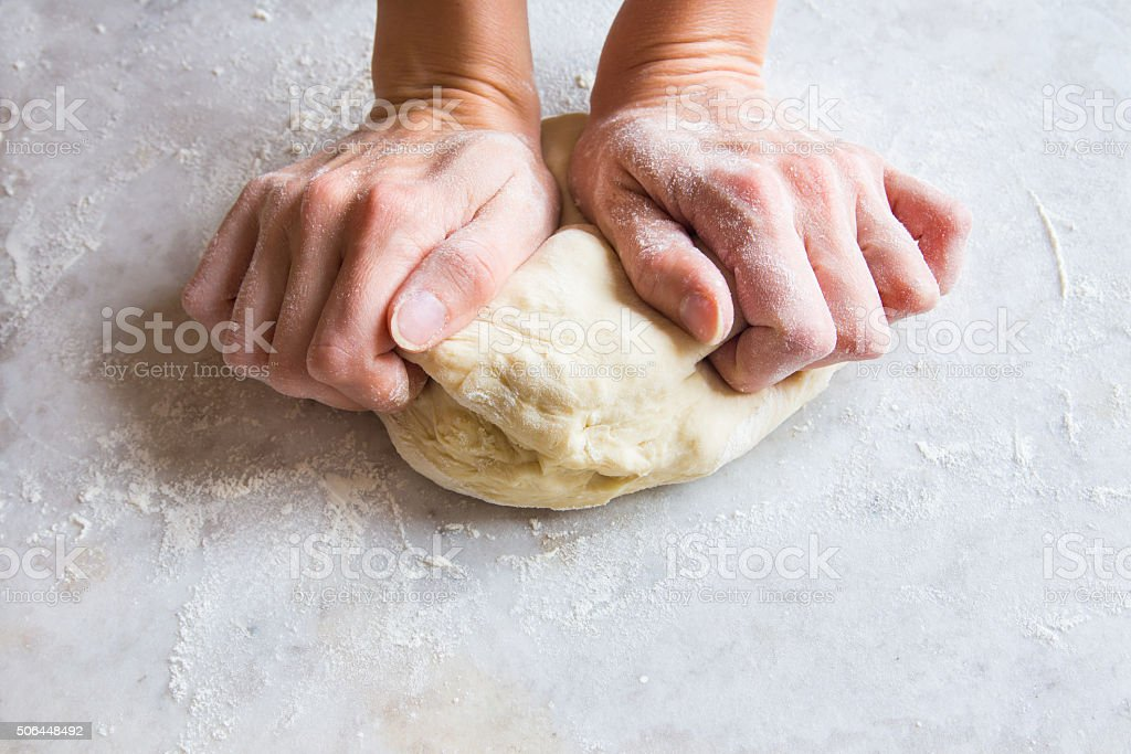 Hands knead dough stock photo