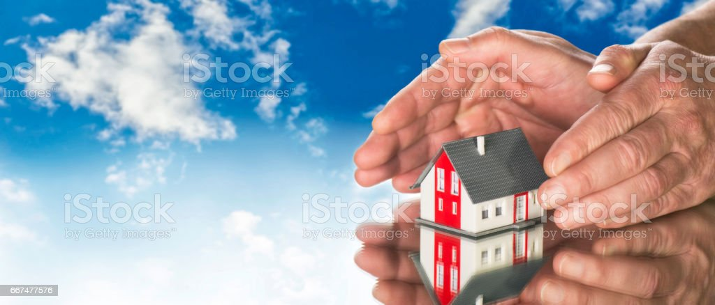 Hands laying protectively around a house stock photo
