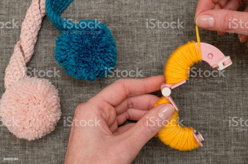 Hands Looping Yellow Yarn Around Pom-Pom Maker stock photo