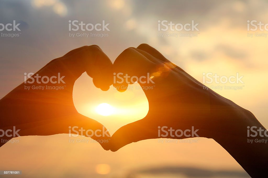 hands make a heart shape against sunset at seaside stock photo