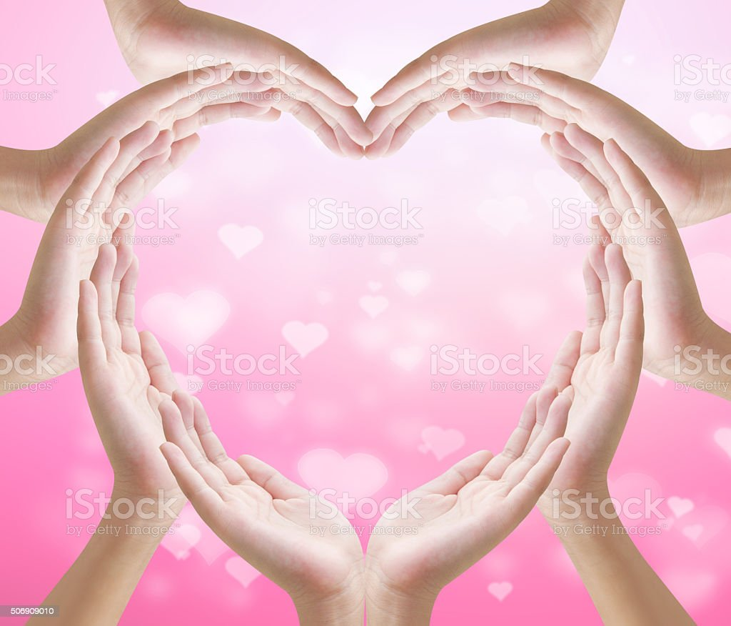 Hands make heart shape on  heart bokeh pink background stock photo