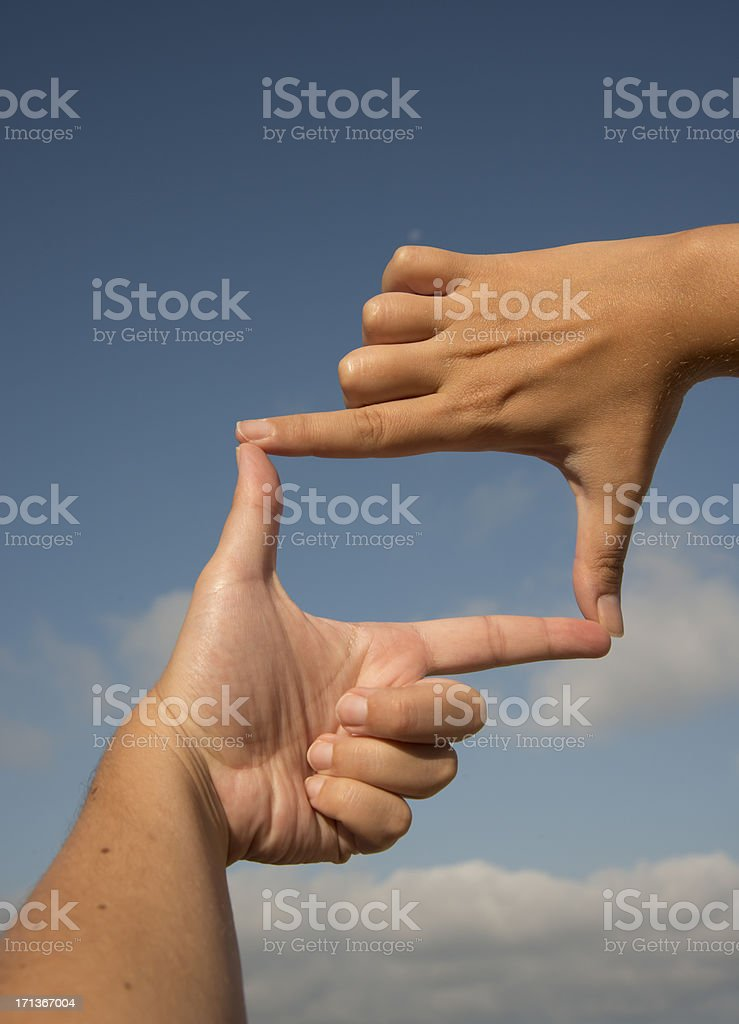 Hands making a frame in front of blue cloudy sky  stock photo