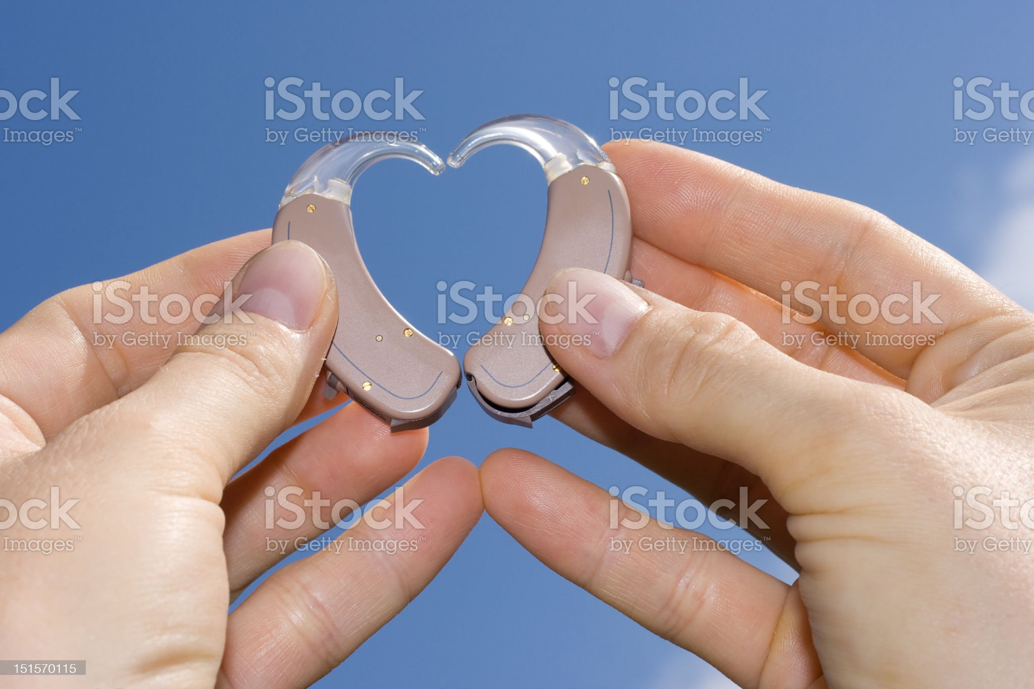 Hands making a heart shape out of hearing aids royalty-free stock photo