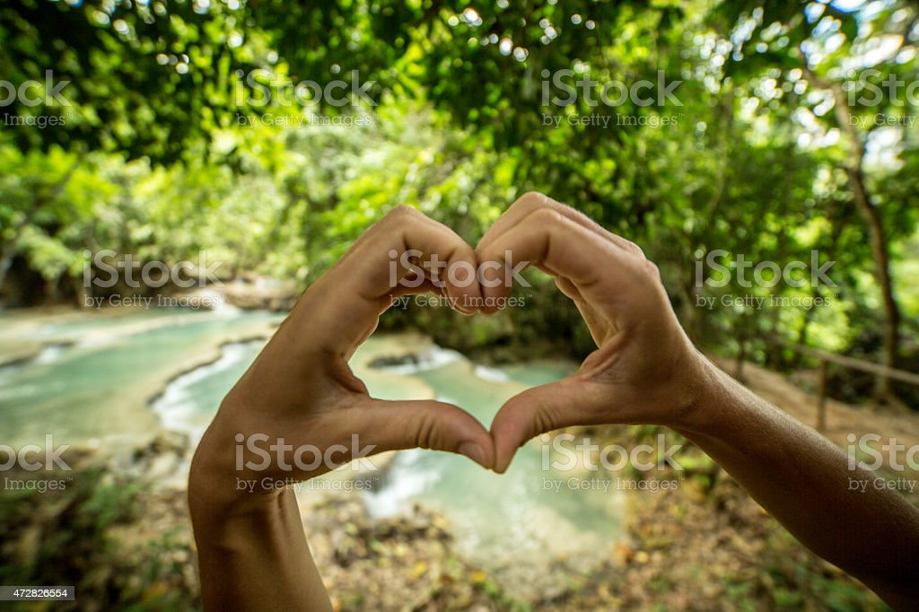 Hands making heart shape with natural pool on background stock photo