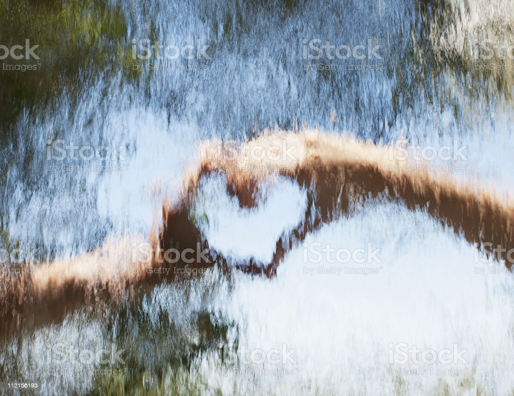 Hands making heart-shape behind glass stock photo