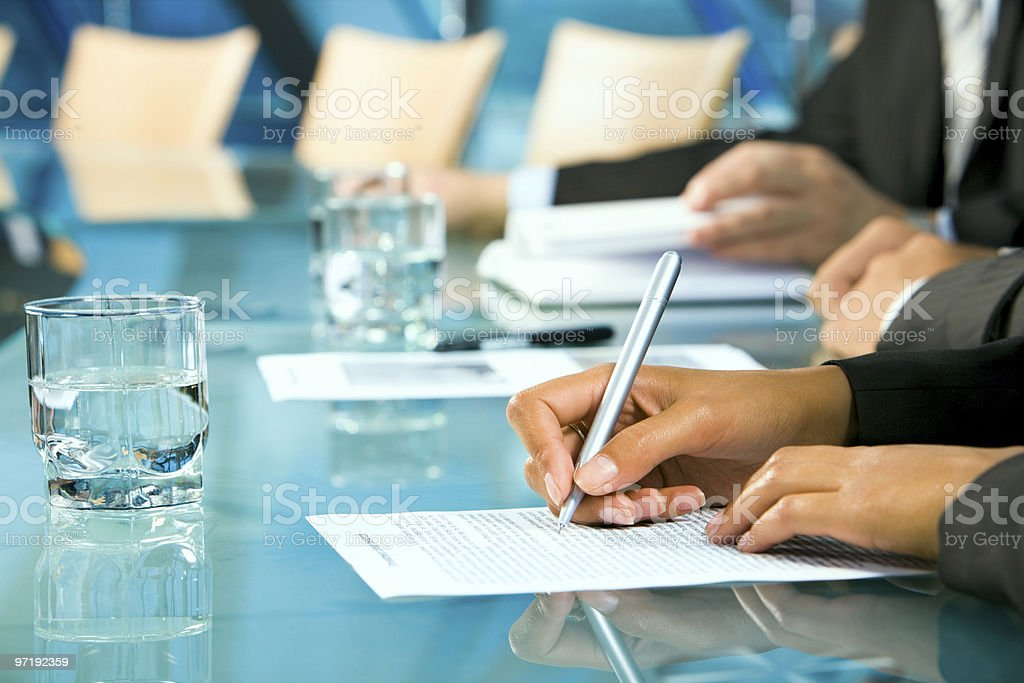 Hands making notes in a business meeting. stock photo
