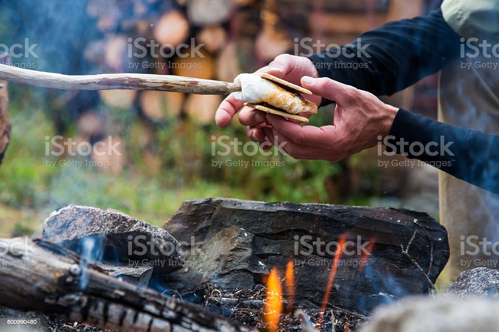 Hands making Smores with marshmallow and chocolate over campfire stock photo