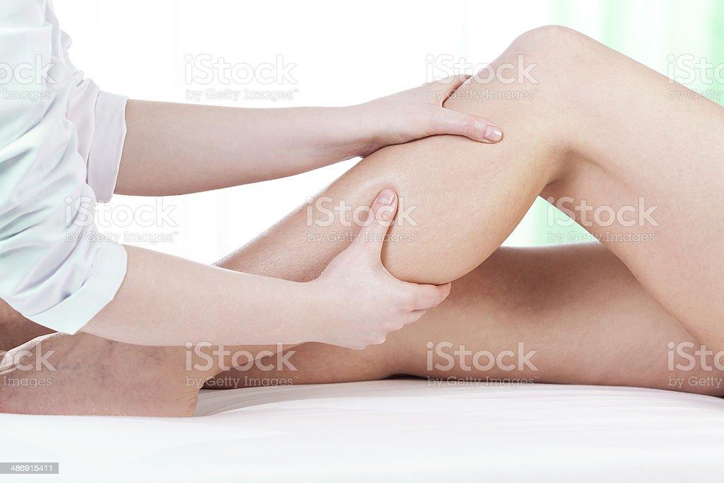 Hands massaging female leg stock photo