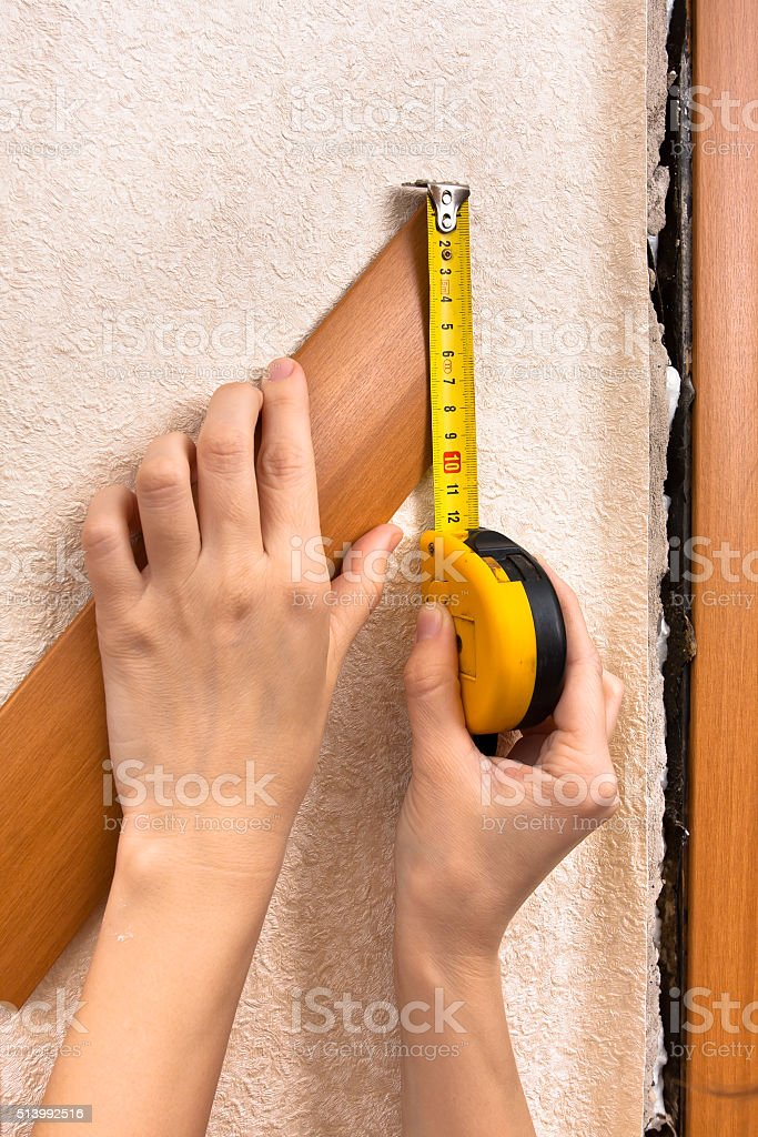 hands measuring width of platband with tape measure stock photo