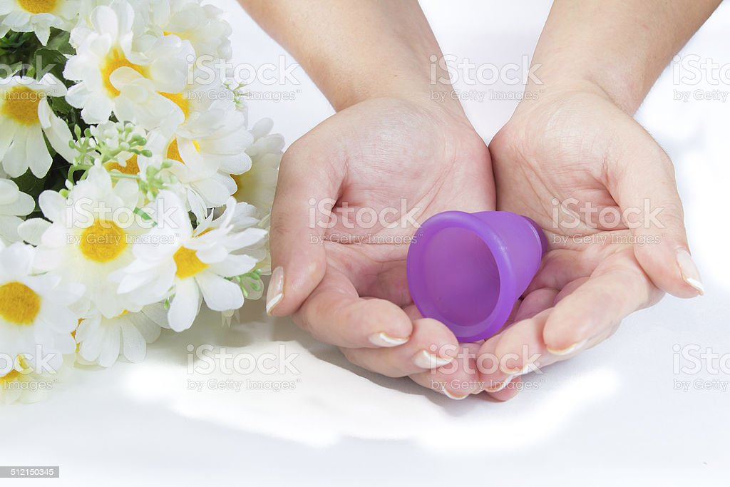 Hands, menstrual cup and flowers. stock photo