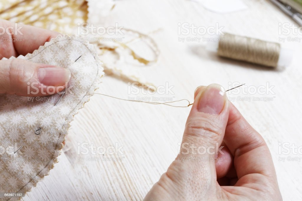 Hands needlewoman holding a needle and thread. stock photo