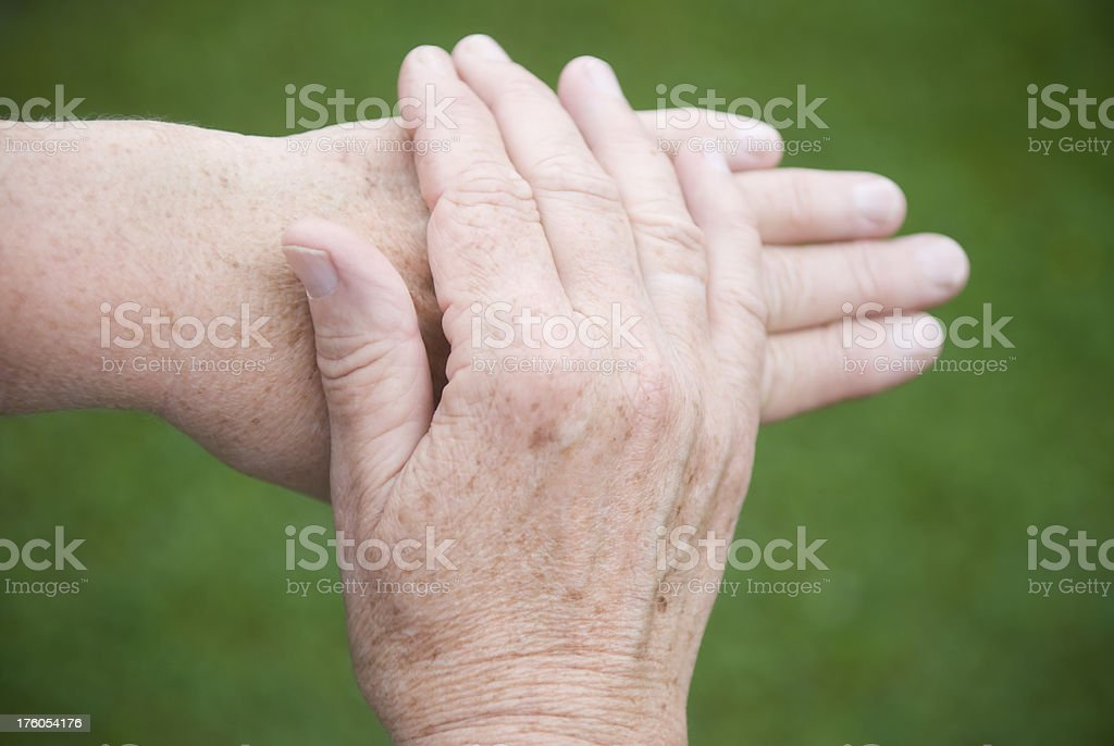 Hands of 60 year-old caucasian woman, stroking, copy space royalty-free stock photo