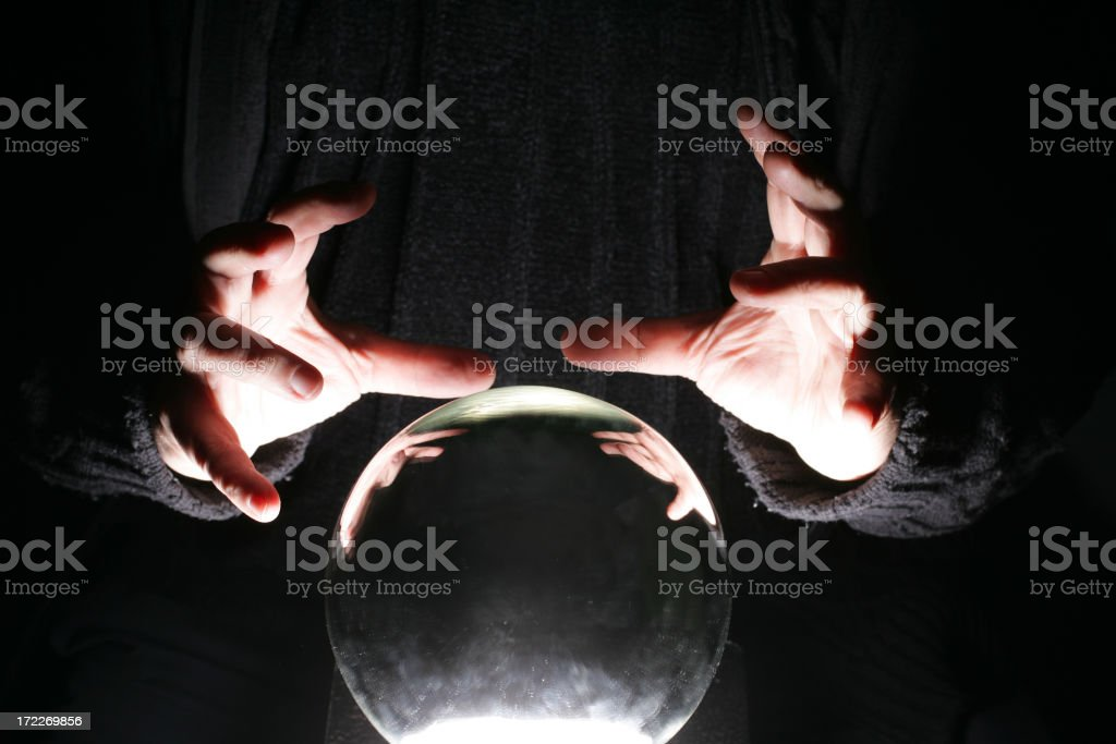 Hands of a black garbed person poised over a crystal ball stock photo