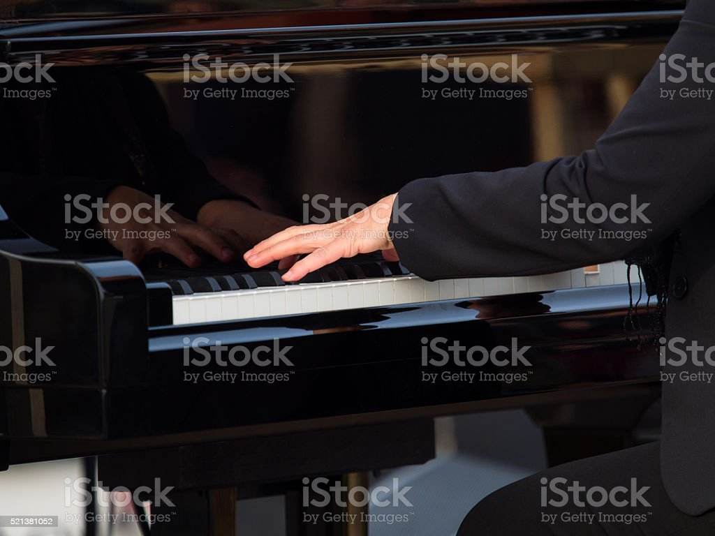 hands of a concert pianist playing a grand piano stock photo