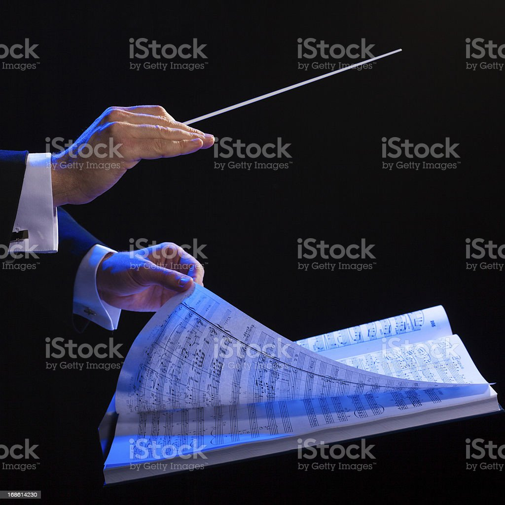 Hands of a conductor with a baton and musical book stock photo