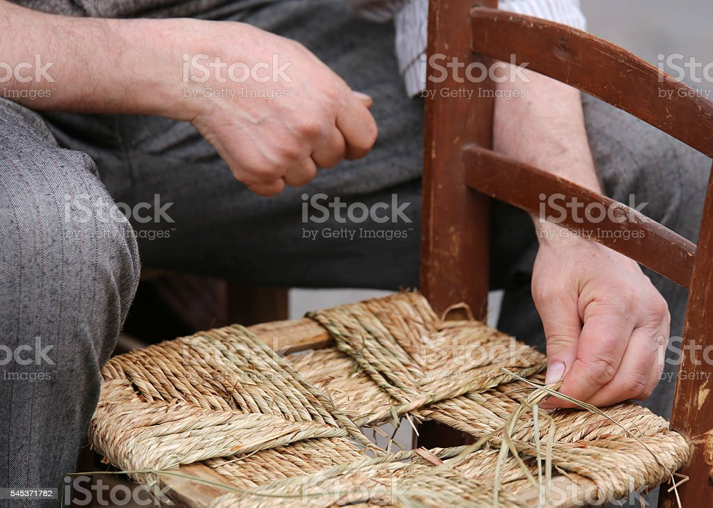 hands of a craftsman while reparing the chair of straw stock photo