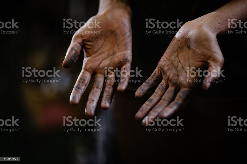 Hands of a craftsperson with grease in between the lines stock photo