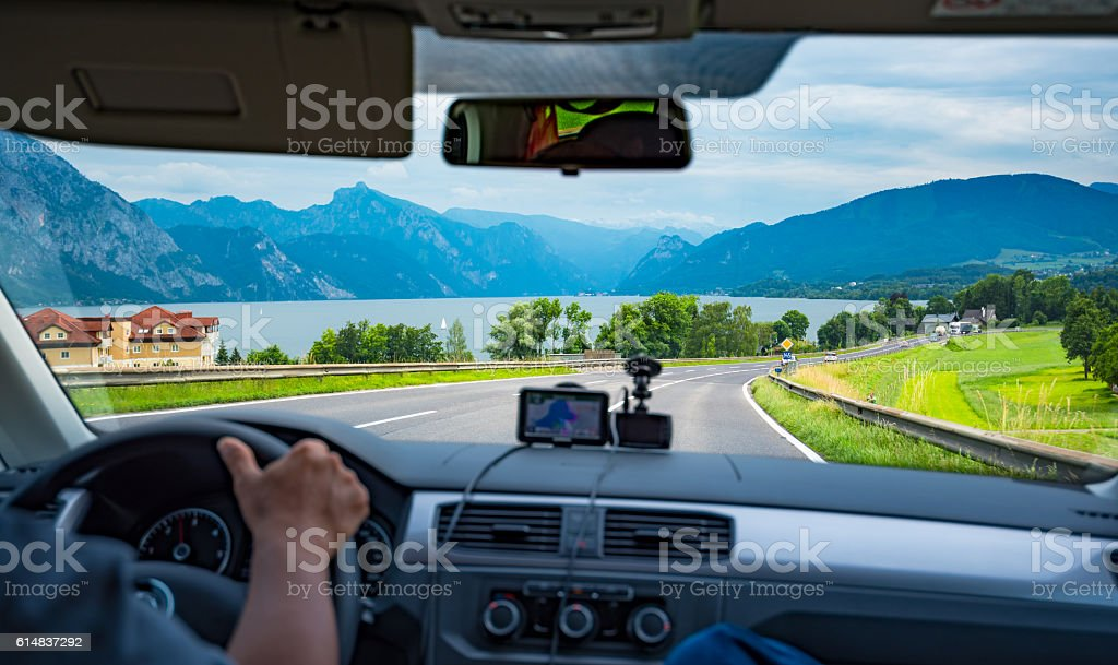 Hands of a driver on steering wheel driving on the road stock photo