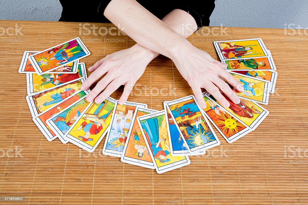 Hands of a fortune teller spreading tarot cards stock photo