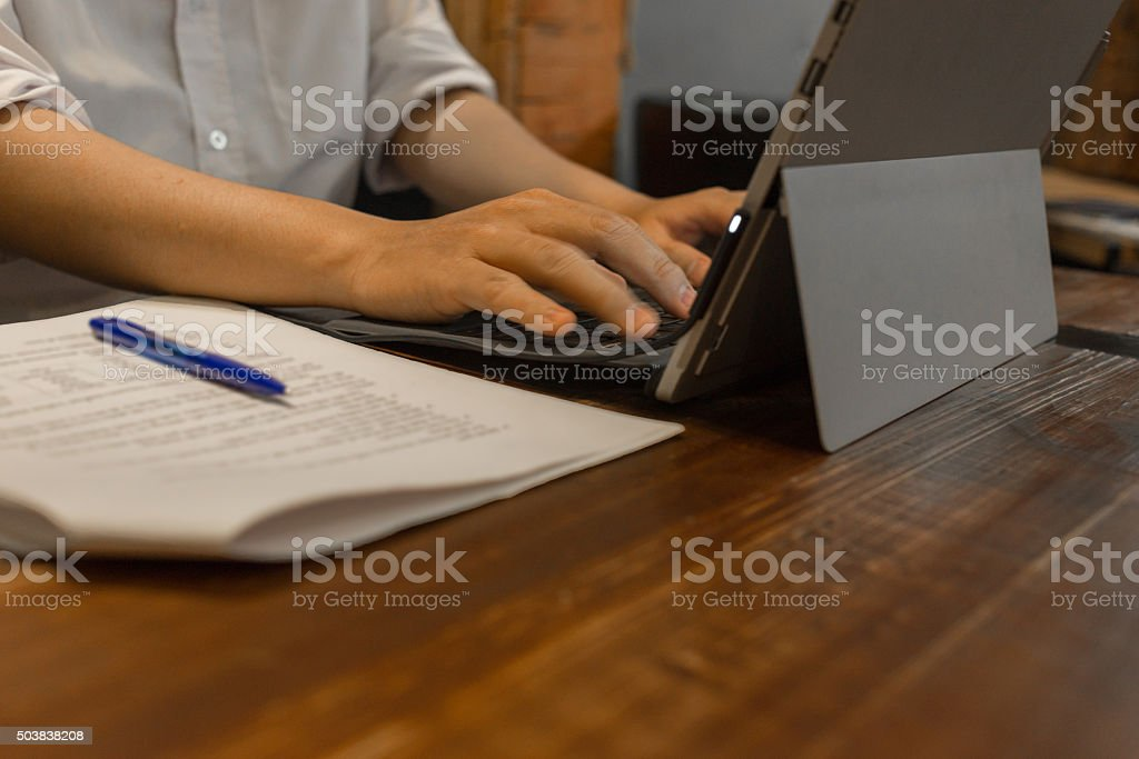 Hands of a male typing on laptop with document beside stock photo