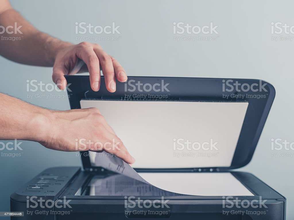 Hands of a man copying a piece of paper stock photo