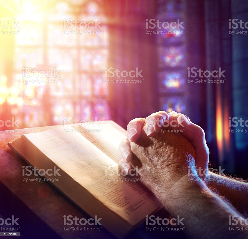 Hands Of A Man Praying With Bible stock photo