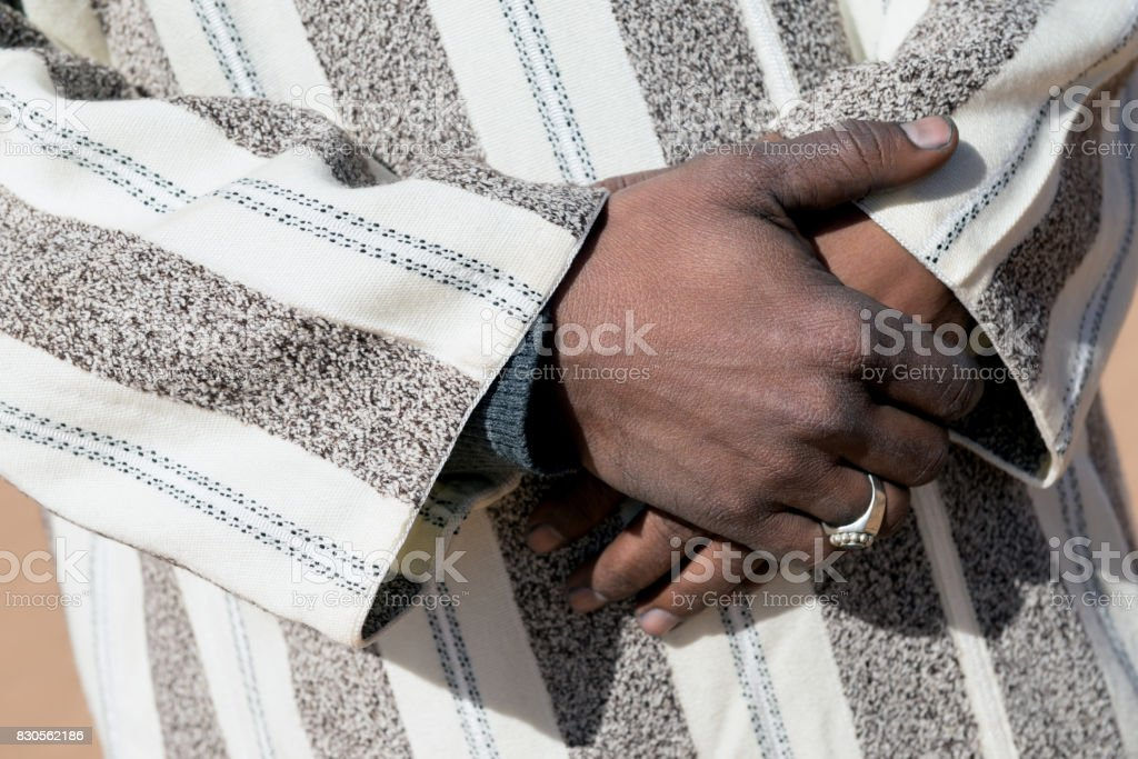 Hands of a moroccan man, dressed in a traditional djellaba. stock photo