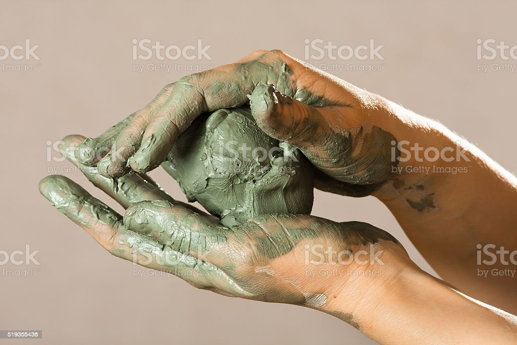 hands of a potter with blue clay stock photo