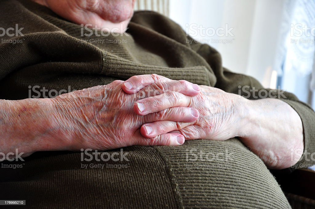 Hands of a senior person crossed on their stomach stock photo