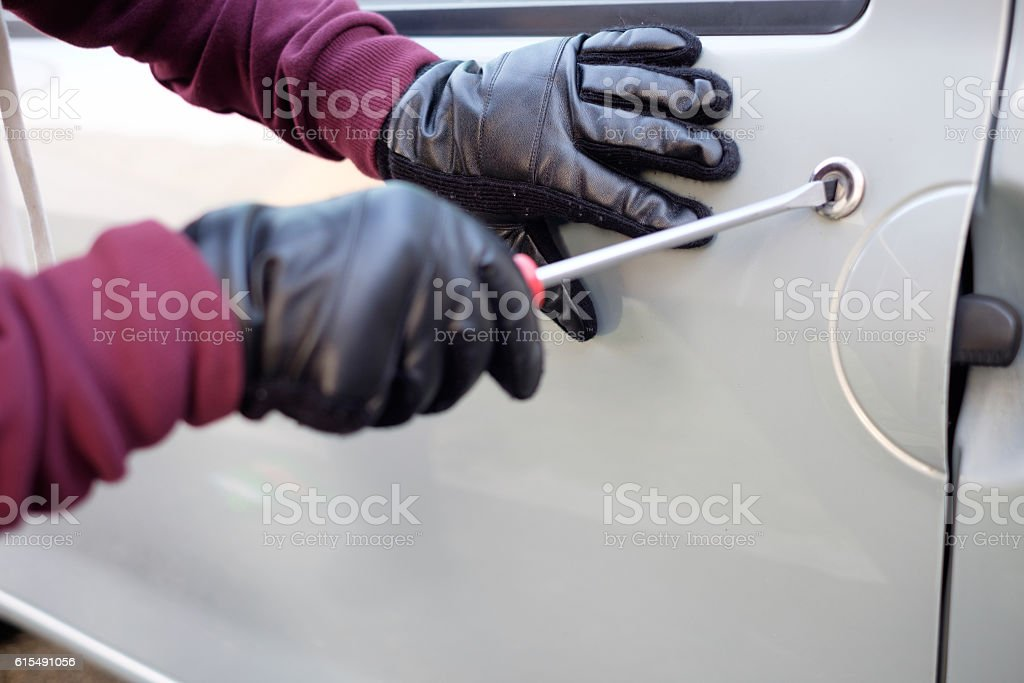 Hands of a thief trying to open a car door stock photo