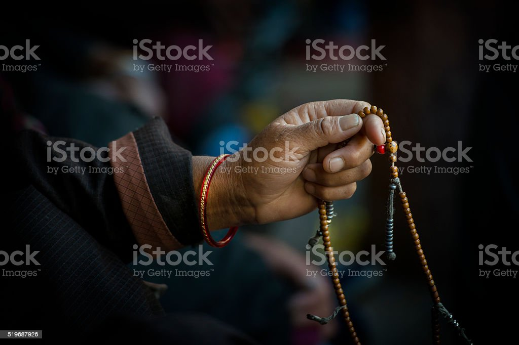Hands of a Tibetan Buddhist with his prayer beads stock photo