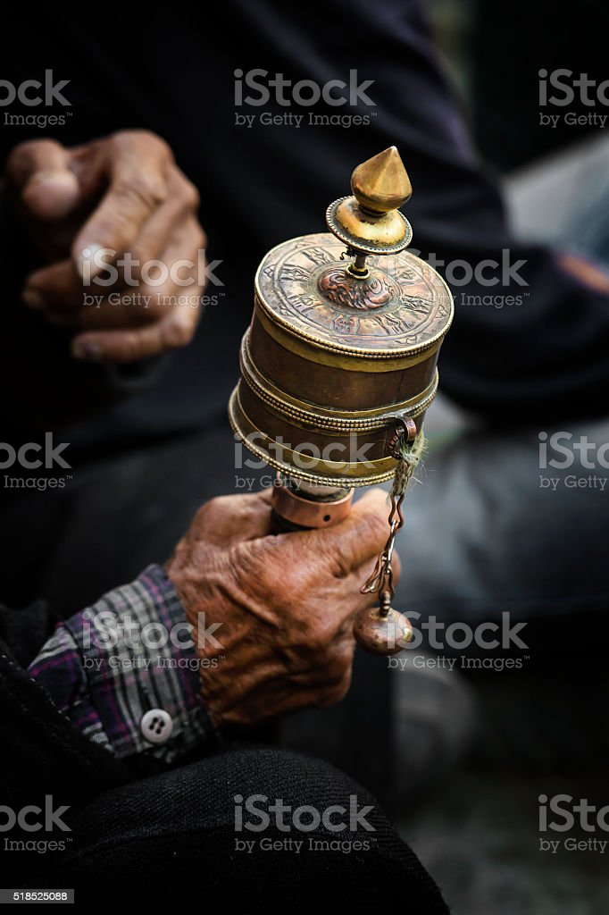 Hands of a Tibetan Buddhist with his prayer wheel stock photo