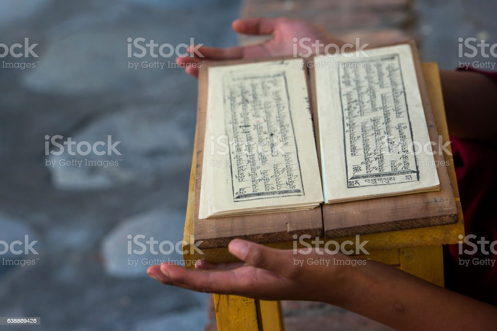 Hands of a Tibetan monk while he is reading prayers stock photo