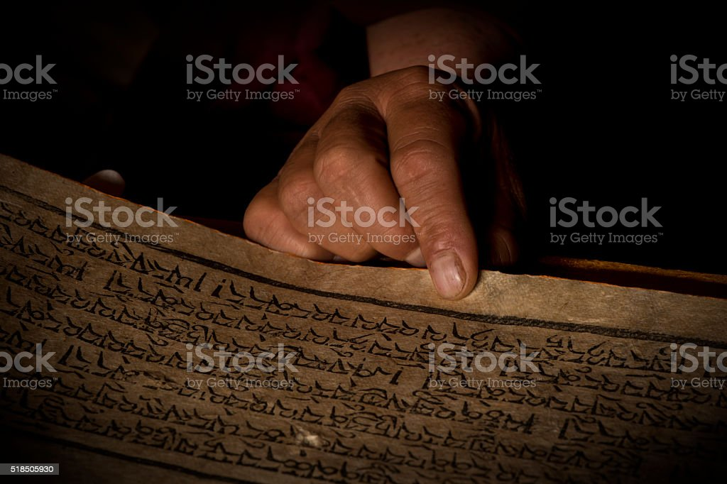 Hands of a Tibetan monk with an acient prayer book stock photo