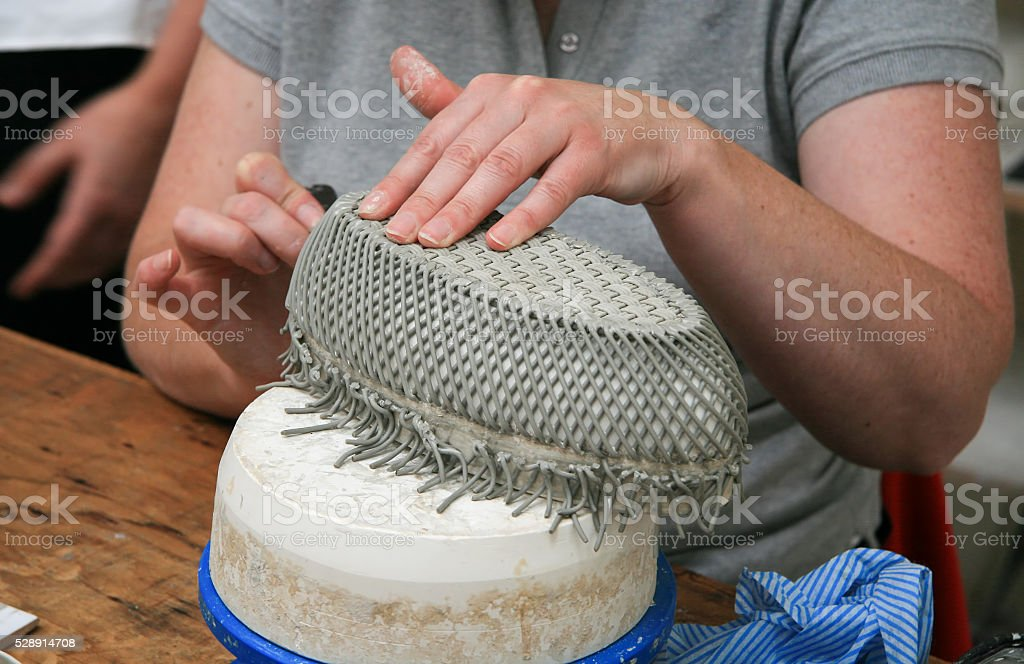 Hands of a woman making a porcelain basket stock photo