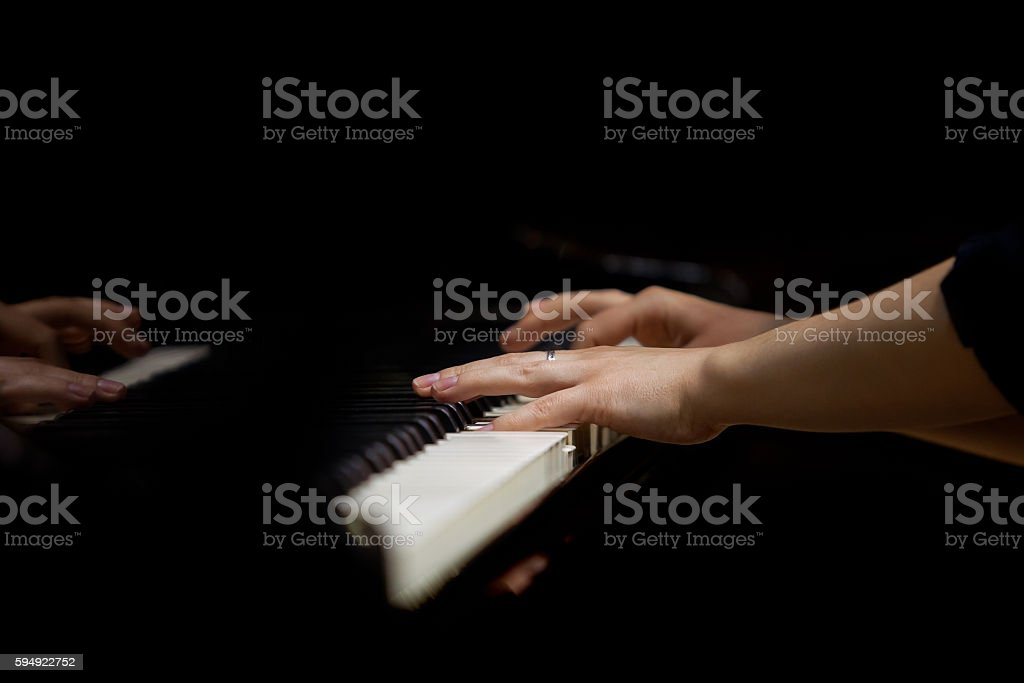 Hands of a woman playing piano closeup stock photo