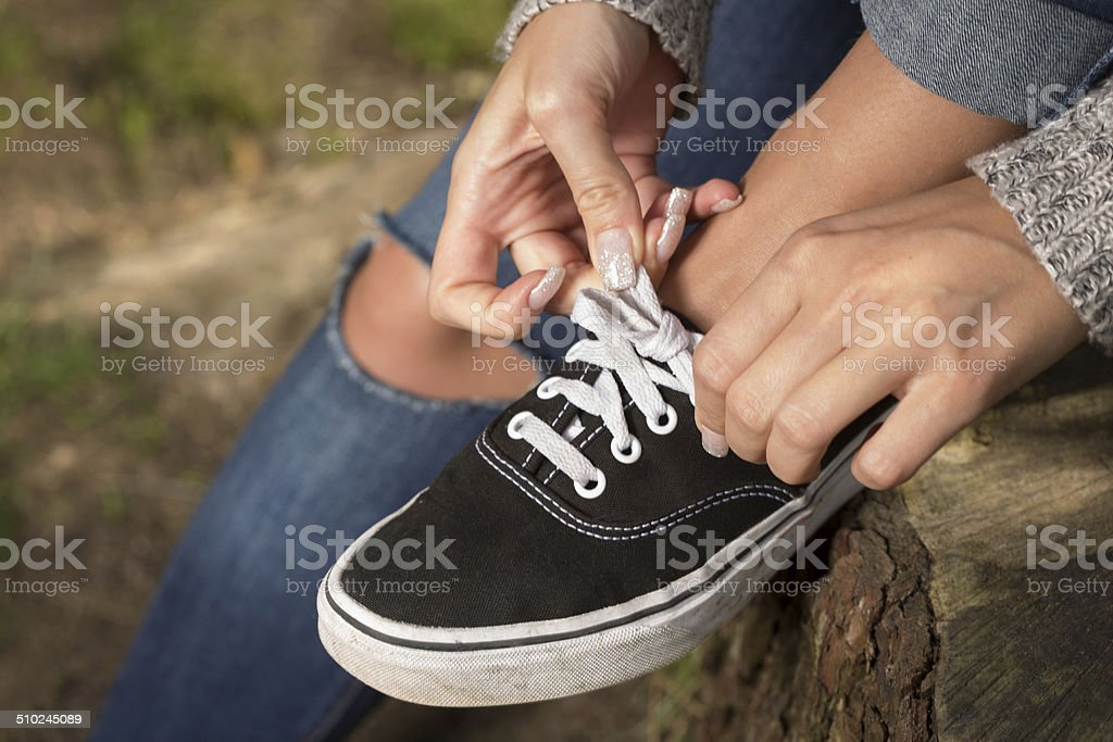 Hands of a woman. Shoelace bow making stock photo