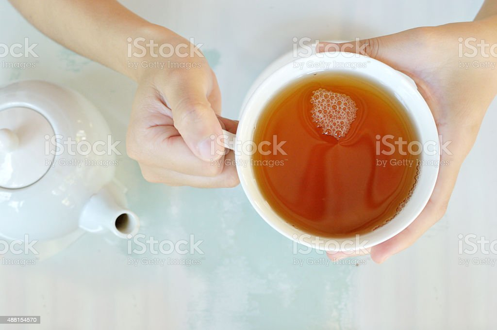 Hands of a woman with a cup of tea stock photo