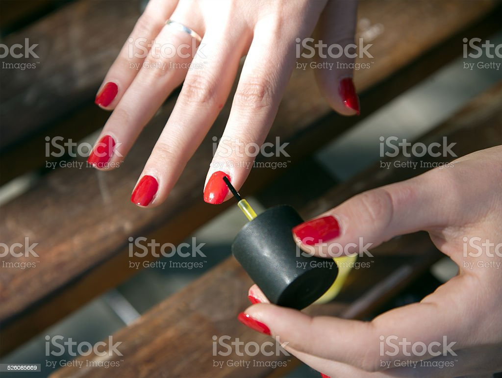 Hands of a young girl who makes a manicure outdoor stock photo