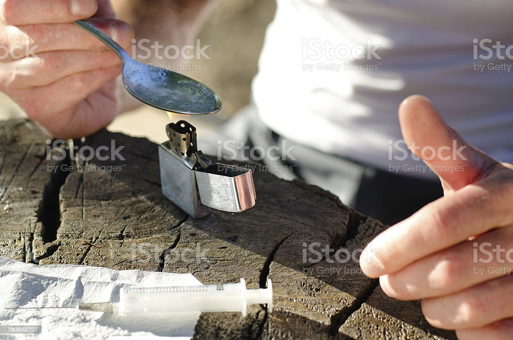 Hands of an addicted man while heating heroin royalty-free stock photo