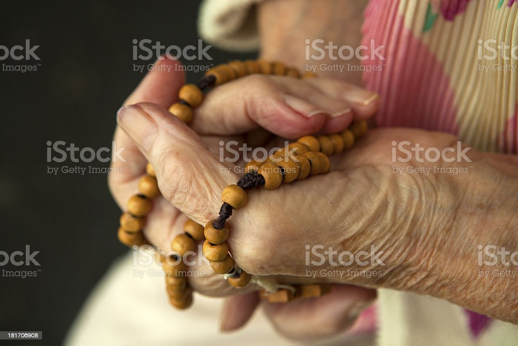 Hands of an old woman and a wooden rosary royalty-free stock photo
