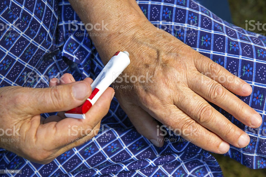 hands of an old woman and hand cream stock photo