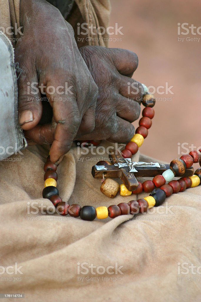 Hands of an old woman with cross royalty-free stock photo