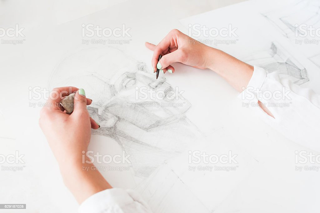 Hands of artist drawing portrait with pencil stock photo