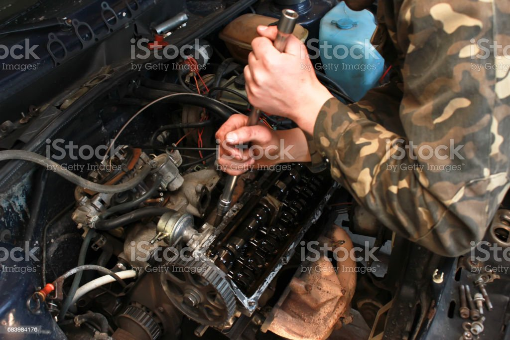 Hands of automechanic, who repairs engine stock photo